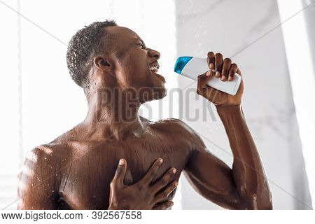 Black Man Singing In Shower Holding Shampoo Bottle Like Microphone Having Fun Bathing Standing In Mo