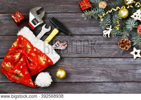 Christmas Construction Tools. A Hammer, A Wrench, An Adjustable Wrench In A Santa Claus Hat Near A S