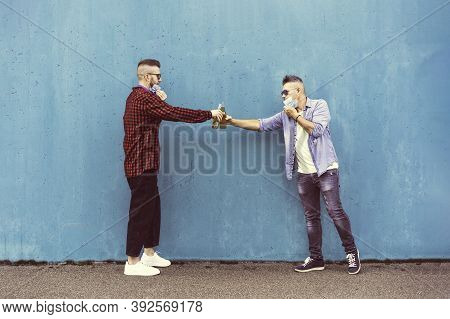 Guys Friends Toasting Beer Bottles With Opened Face Masks Against Blue Wall Background - New Normal