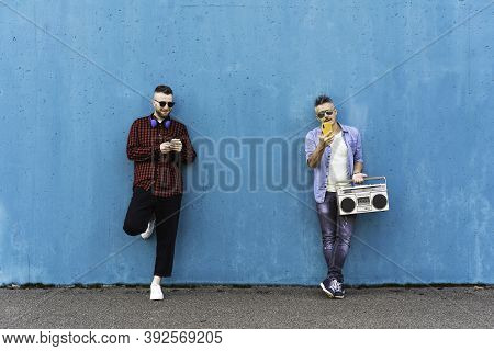 Cool Men Looking At Mobile Phone Lean Against Blue Wall - Couple Of Influencer Guys Listening Music