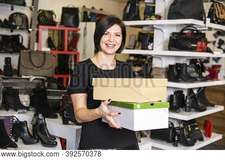 A Sale, Shopping And People Concept Happy Young Woman Or Shop Assistant With Shoe Boxes At Store