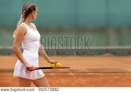 Tennis Player In White Sportswear Preparing To Serve Tennis Ball, Training Before Match