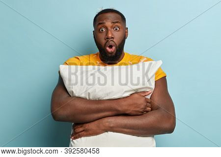 Morning And Oversleep Concept. Emotive Stupefied Dark Skinned Bearded Guy Embraces White Soft Pillow