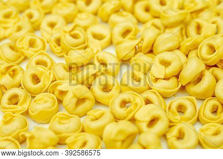Close-up Photo. Background Of Dried Tortellini. Full Frame Pattern. Italian Dumplings Made From Unle