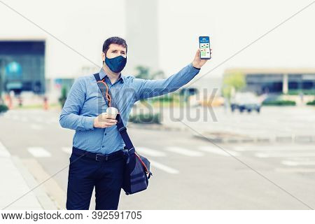 Man Passenger With Protective Face Mask Using Mobile Taxi App Waiting Cab Or Ride Share With Hand Up