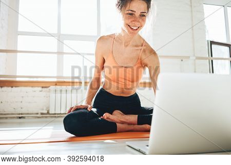 Yoga Woman Instructor Taking Online Lesson Using Video Call In Laptop. Fitness Instructor Leads A Le