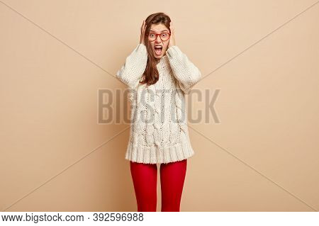 Emotional Frustrated Woman Cries Desperately, Covers Ears And Shouts Loudly, Dressed In White Long J