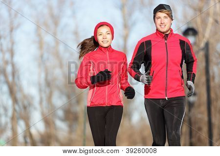 Running. Runners jogging outside. Young couple training outside in warm sport clothing outfit. Beautiful young interracial couple, Asian woman and Cauasian man.
