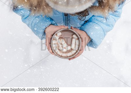 Little Girl Drinks Hot Chocolate, Cocoa, Marshmallows From Thermos Metal Cup, Mug . Warm Blue Jacket