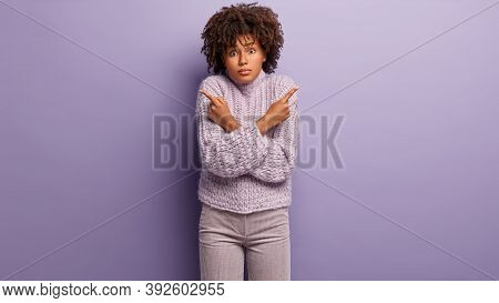 Confused Hesitant Dark Skinned Female Model Crosses Hands Over Chest, Points Both Fore Fingers At Di