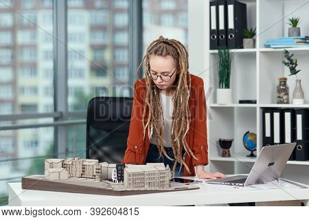 Experienced Female Architect With Dreadlocks Working With Cardboard Model Of Residential Area In Arc