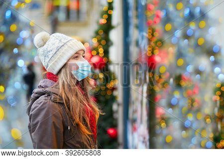 Girl Wearing Face Mask On A Parisian Street Or At Christmas Market Looking At Shop Windows Decorated