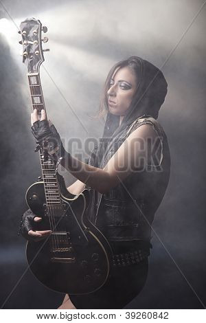 Strong Expressive Girl Posing With A Guitar