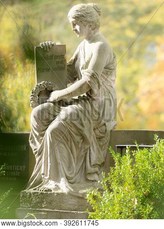 Woman Statue With Book In Hands Sit At Family Grave Stone.  Female Statue Secure Tombstones.  24th O