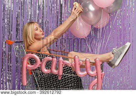 Beautiful Blonde Woman Sits In Shopping Cart, Makes Selfie On Camera, Wears Sportshoes, Festive Dres