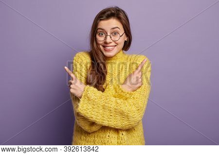 Glad Lovely Dark Haired Woman Points Fingers To Both Sides, Shows Different Direction, Wears Yellow