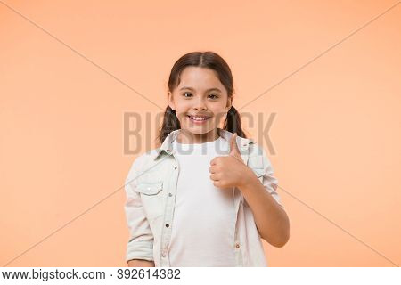 Good Quality. Kid Girl Shows Thumb Up Gesture Recommends Yellow Background. Child Highly Recommend W