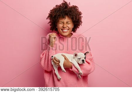 Cheering Optimistic Woman Has Toothy Smile, Clenched Fist, Holds White And Black Small Pet With Soft