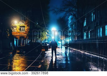 Silhouette Of Alone Stranger In Hood At Night City Street In Rain. Creepy Killer Or Stalker, Crimina