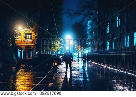 Silhouette Of Alone Stranger In Hood At Night City Street In Rain. Creepy Killer Or Stalker, Crimina