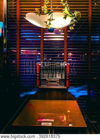 11/2/2020: An Old Vintage Looking Table And Lamp With An 1960s Looking Jukebox Radio In A Windowsill
