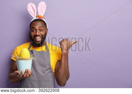 Plump Glad Afro American Man Points Away With Thumb, Glad To Advertise Something, Holds Pot Containi