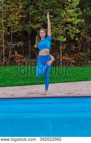 Young Woman Doing Yoga Exercises Near The Swimming Pool Ourdoors.
