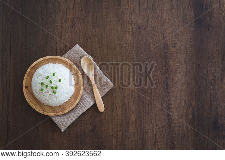 Cooked White Rice In A Wooden Dish With Green Onion Sliced On Top With Wooden Spoon, And Placemat On