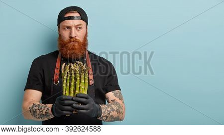 Indoor Shot Of Male Chef Holds Spring Vegetable, Asparagus For Preparing Delicious Salad, Thinks Whi