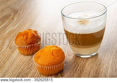 Two Orange Muffins, Transparent Glass With Latte-macchiato On Wooden Table