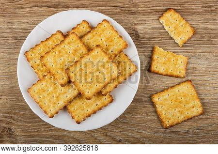 Crunchy Cookies With Sesame In White Plate, Broken Cracker On Wooden Table. Top View