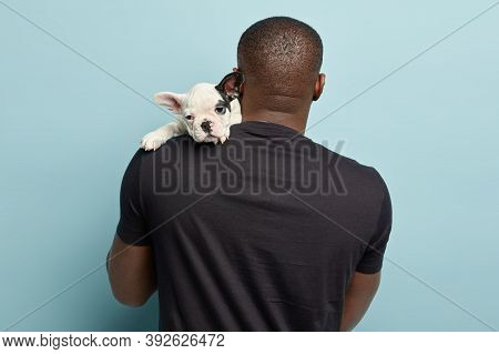 Black Plump Man Stands Back To Camera, Carries Small Puppy On Shoulder, Going To Have Walk Together,