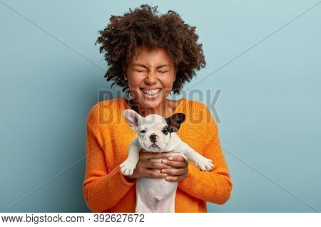 Joyous Black Lady With Curly Hairstyle, Closes Eyews In Pleasure, Holds Small Dog, Going To Give Foo