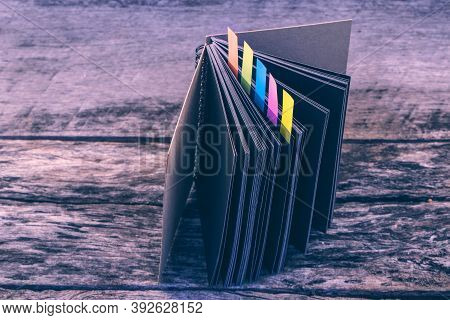 Colorful Bookmarks For Documents With Black Diary On Wooden Background. Closeup Of Color Tabs For Bo