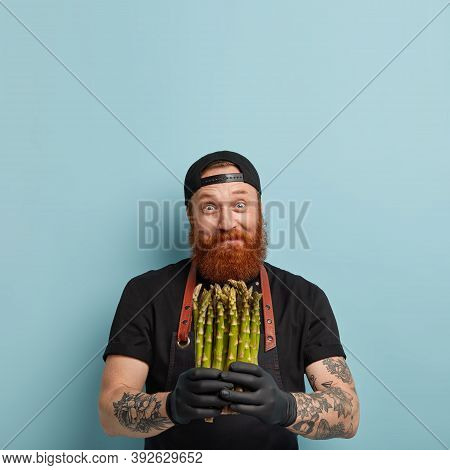 Eating Vegetables Concept. Delighted Joyful Bearded Man Holds Bunch Of Delicacy Fresh Green Asparagu