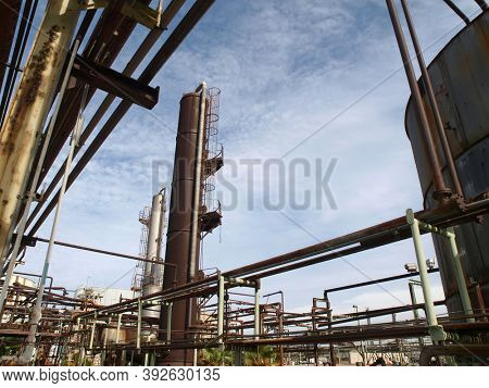 View of old rusty oil and petrochemical industrial refinery pipes.