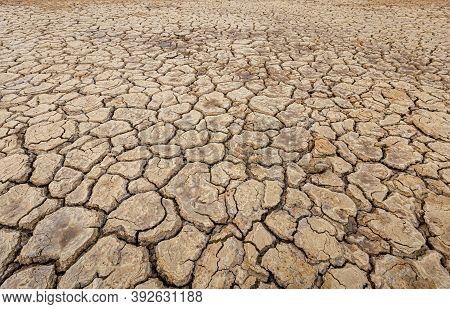 Brown Dry Soil Or Desert Cracked Ground Texture Background,land Arid Earth Warming.