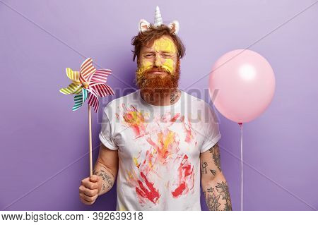 Studio Shot Of Dissatisfied Redhead Man Holds Toy Windmill And Helium Balloon, Has Face Dirty With Y