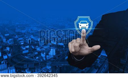 Businessman Pressing Car With Shield Flat Icon Over Modern City Tower, Street, Expressway And Skyscr