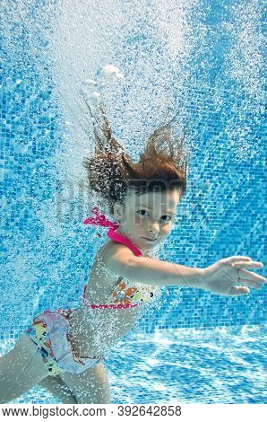 Child Swims In Swimming Pool Underwater, Little Girl Jumps, Dives And Has Fun Under Water, Kids Fitn