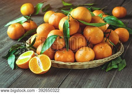 Ripe Mandarin Fruit Peeled Open And Place On Old Rustic Look Timber With Group Of Mandarin Fruits An