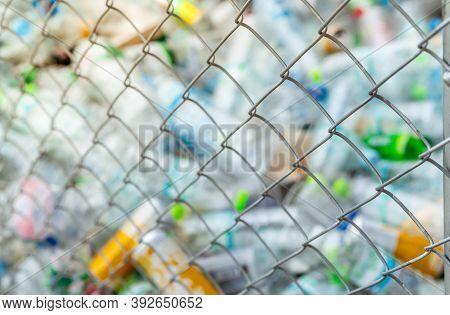Blurred Photo Of Pile Of Empty Water Plastic Bottle In Mesh Fence Recycle Bin. Plastic Bottle Waste