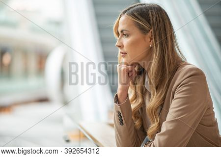 Thoughtful businesswoman in a thoughtful expression in a bright mall