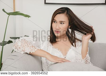 A Woman Sitting Dazed And Distracted On The Gray Sofa At Home. Girl Pulling Her Hair With Her Hand.