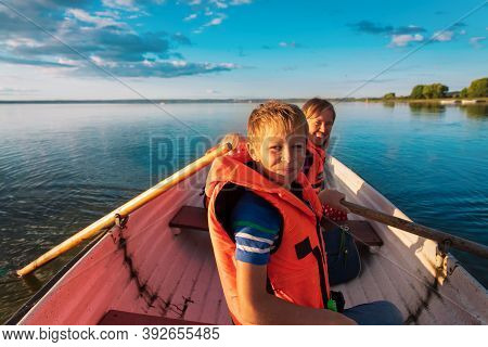 Happy Family In Life Jackets On Boat Ride In Lake