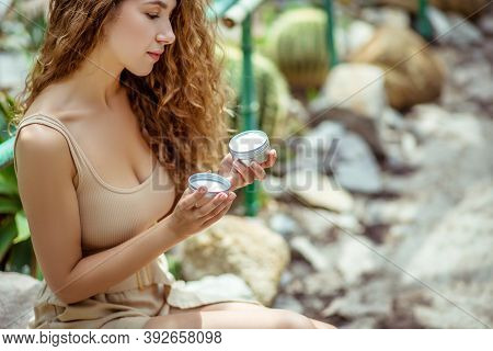 Long-haired Young Woman Holding A Jar Of Cream