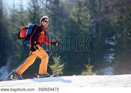 Young Smiling Man Skier Doing Ski Touring At Winter Mountains On A Sunny Day. Snow And Winter Activi