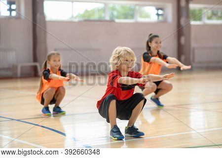 Three Kids Exercising In The Gym And Doing Squats