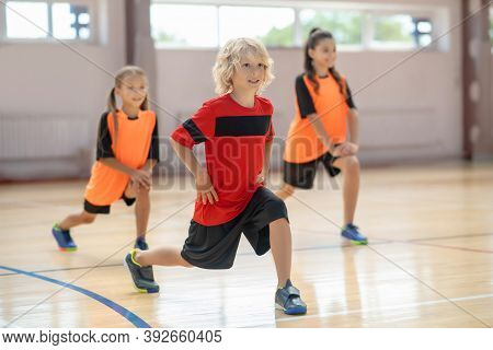 Kids Exercising In The Gym And Doing Lungings Forward