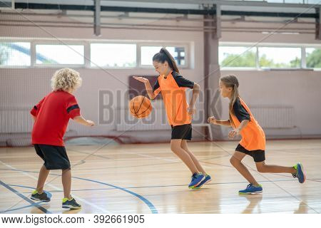 Kids In Bright Sportswear Playing Basketball Together And Feeling Involved